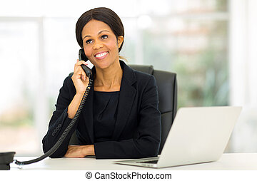 middle aged african businesswoman talking on the phone