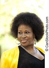 Middle-aged Black woman outdoors Portrait yellow jacket