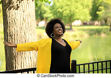 Middle Aged Black woman with arms outstretched