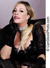 Middle-Aged Blond Caucasian Woman Sitting In Black Lacy Lingerie