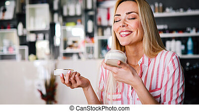 Middle-aged blond woman putting cosmetics