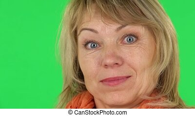 Middle aged blonde woman is looking in surprise at the camera. Close-up. Green screen