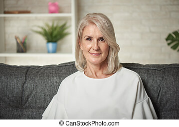 Middle aged blonde woman is sitting on a sofa at home