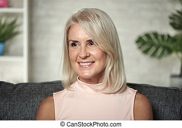 Middle aged blonde woman is smiling sitting on a couch