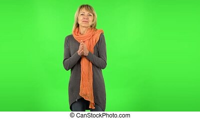 Middle aged blonde woman is waiting in anticipation with pleasure. Green screen