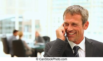 Middle aged business man talking on the phone during a meeting