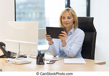 Middle aged business woman using digital tablet at office