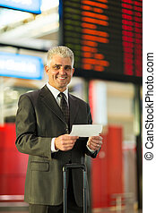middle aged businessman holding air ticket