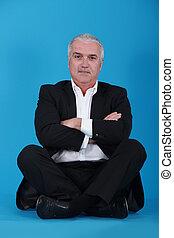 Middle-aged businessman sat cross-legged