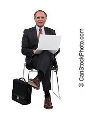 Middle-aged businessman sat in chair using laptop