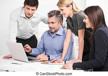 Middle aged businessman showing company strategy on laptop. Smiling perspective business team looking at laptop with great interest