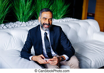 Middle-aged businessman using mobile phone in modern office on sofa