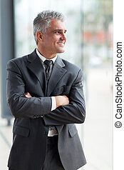 middle aged businessman with arms crossed