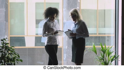 Focused middle aged businesswoman reviewing research report of african american young female employee on tablet, making edits, giving tasks, satisfied with good job done shaking hands near big window.