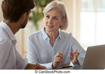 Middle aged businesswoman manager speaking to businessman client teaching intern