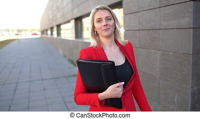Middle-aged Businesswoman wearing red jacket walking outside of an office building looking at camera. Slow motion.