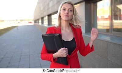 Middle-aged Businesswoman wearing red jacket walking outside of an office building. Slow motion.