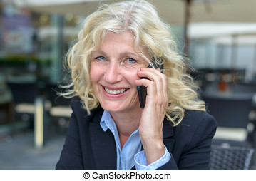 Middle-aged businesswoman talking on a mobile phone with a...