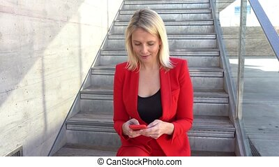 Middle-aged Businesswoman using smartphone outdoors. Blonde ...