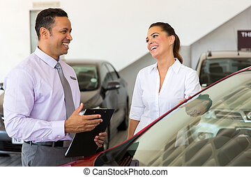 middle aged car salesman talking to a customer