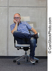 middle-aged cauaciasn man wrong sitting posture on office chair