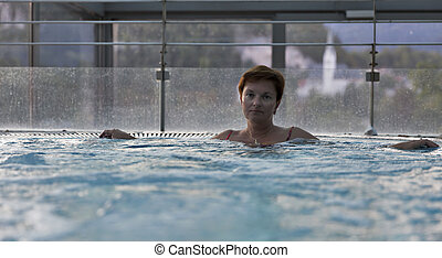 Middle aged Caucasian woman relaxing in jacuzzi