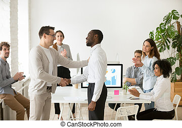 Middle aged CEO congratulating African American manager with pro