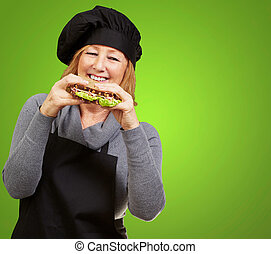 Middle aged cook woman holding a vegetal sandwich over green...