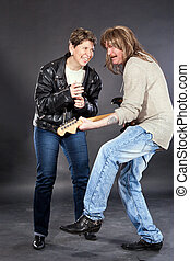 Middle aged couple acting as rock band with electric guitar and microphone in studio