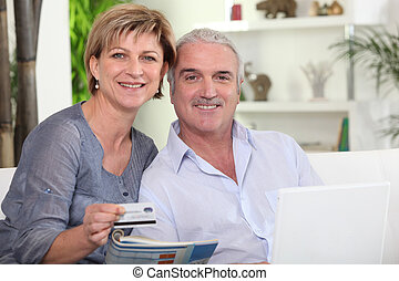 middle-aged couple all smiles with computer sharing moment