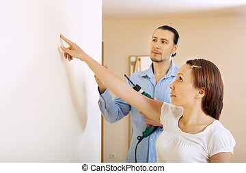 Middle-aged couple choosing point for hole in  wall