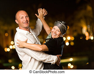 Middle-aged couple dancing waltz at night