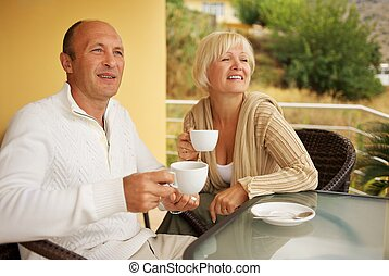 Middle-aged couple drinking caffee outdoors