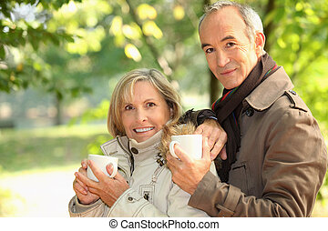 Middle-aged couple drinking coffee in park