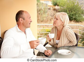 Middle-aged couple drinking coffee outdoors
