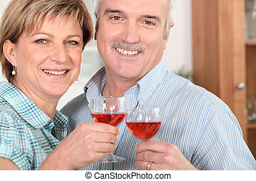 Middle-aged couple drinking wine in kitchen