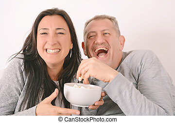 Middle-aged couple eating popcorn and watching a movie