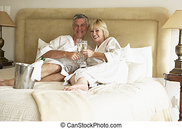 Middle Aged Couple Enjoying Champagne In Bedroom