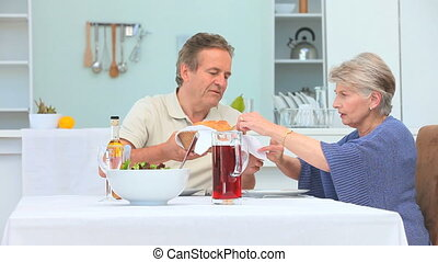 Middle aged couple having a lunch in the dinning room