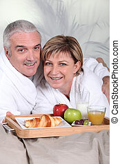 middle-aged couple having breakfast in bed