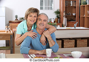 Middle-aged couple having breakfast together in kitchen