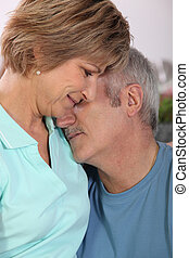 Middle-aged couple hugging at home