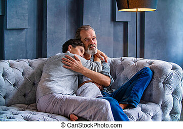 couple hugging while sitting on the couch