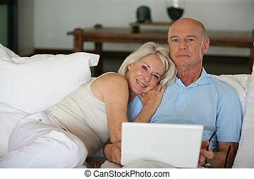 Middle-aged couple in bed with laptop