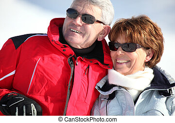 Middle-aged couple on a snowy mountain