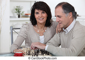 Middle-aged couple playing chess