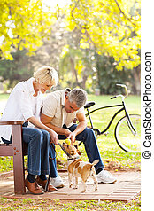 middle aged couple playing with pet dog outdoors