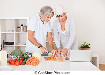 Middle-aged couple preparing a meal - High angle view of an...