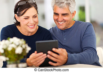 middle aged couple reading emails - middle aged couple...