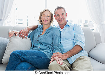 Middle aged couple relaxing on the couch smiling at camera...